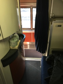 Entrance from aisle, sink on the left hand side and a half-height wardrobe on the right hand side